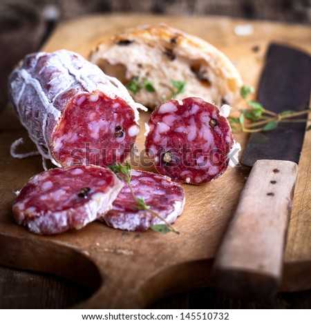 Salami with homemade Ciabatta and herbs on rustic wooden board - stock photo