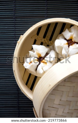 salapao dim sum in bamboo mat on black background - stock photo