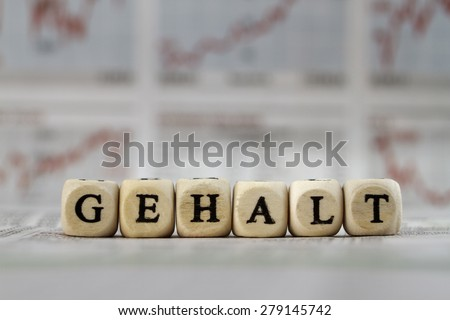 Salary word built with letter cubes on newspaper background - stock photo