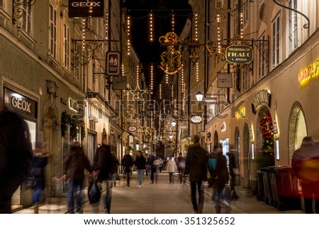 SALBURG, AUSTRIA - 11TH DECEMBER 2015: A view along Getreidegasse in Salzburg at night during the Christmas season. People, shops and buildings can be seen. - stock photo