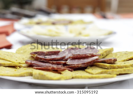 Salchichon slices, typical spanish sausage, beside artisan sausage made of meat, eggs and several spices