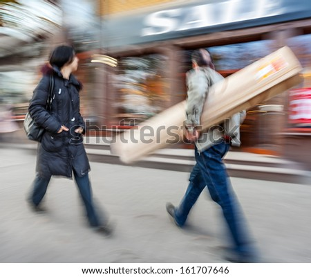 Sale. A man with a big roll and a young woman going shopping with discounts. Intentional motion blur - stock photo