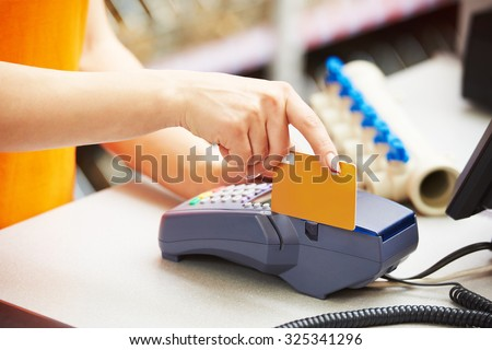 sale assistant cashier accepting credit bank card and using payment terminal for purchase - stock photo