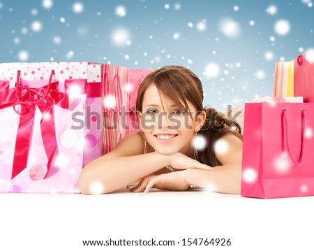 sale, christmas, x-mas and holidays concept - happy girl with shopping or gift bags