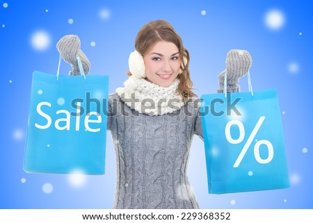 sale concept - young beautiful woman with shopping bags over snow christmas background - stock photo
