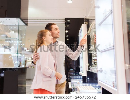 sale, consumerism and people concept - happy couple pointing finger to shopping window at jewelry store in mall - stock photo