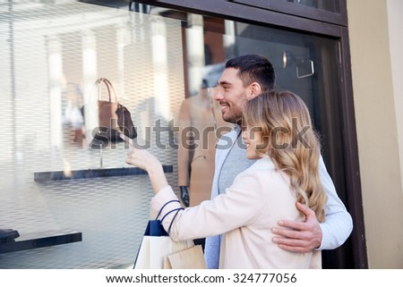 sale, consumerism and people concept - happy couple with shopping bags pointing finger to shop window on city street - stock photo