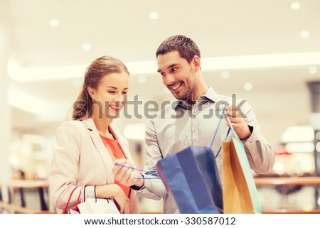 sale, consumerism and people concept - happy young couple showing content of shopping bags in mall - stock photo