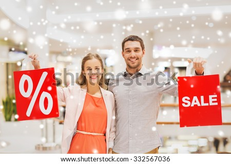 sale, consumerism and people concept - happy young couple with red shopping bags in mall with snow effect - stock photo