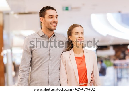 sale, consumerism and people concept - happy young couple with shopping bags in mall - stock photo