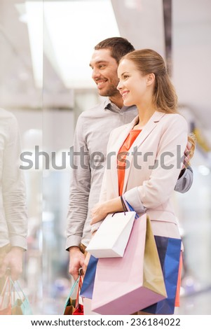 sale, consumerism and people concept - happy young couple with shopping bags looking to shop window in mall - stock photo