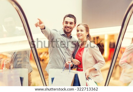 sale, consumerism and people concept - happy young couple with shopping bags rising on escalator and pointing finger in mall - stock photo