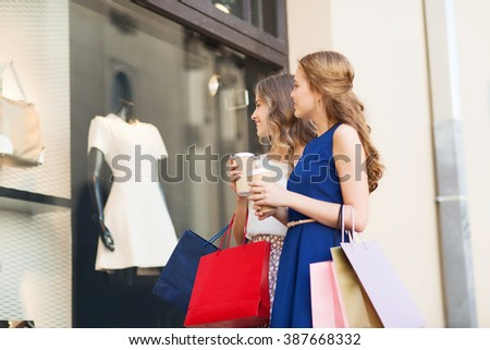 sale, consumerism and people concept - happy young women with shopping bags and coffee paper cups looking at shop window outdoors - stock photo