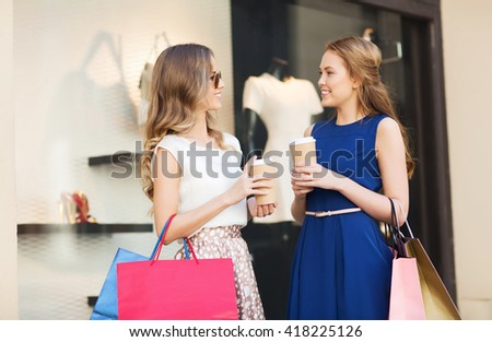 sale, consumerism and people concept - happy young women with shopping bags and coffee paper cups talking at shop window in city - stock photo