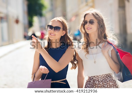sale, consumerism and people concept - happy young women with shopping bags pointing finger in city - stock photo