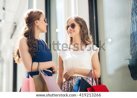 sale, consumerism and people concept - happy young women with shopping bags talking at to shop window in city - stock photo