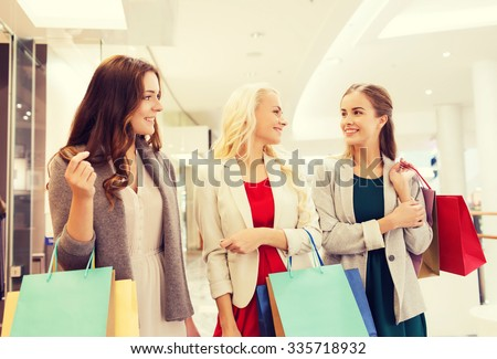 sale, consumerism and people concept - happy young women with shopping bags talking in mall - stock photo