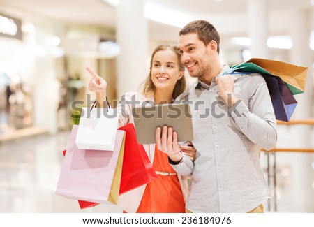sale, consumerism, technology and people concept - happy young couple with shopping bags and tablet pc computer pointing finger in mall - stock photo
