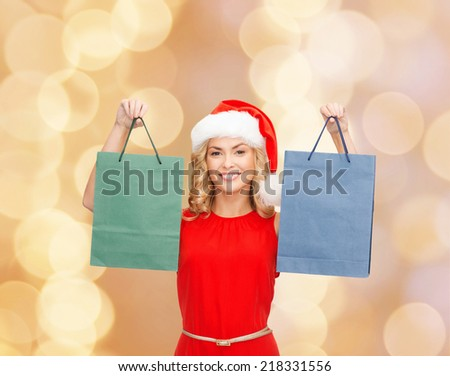 sale, gifts, christmas, holidays and people concept - smiling woman in red dress and santa helper hat with shopping bags over beige lights background
