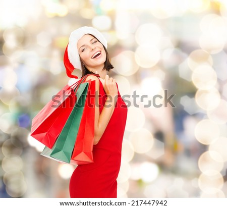sale, gifts, christmas, holidays and people concept - smiling woman in red dress with shopping bags over lights background