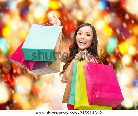 sale, gifts, christmas, x-mas concept - smiling woman in red dress with colorful shopping bags