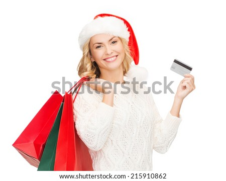 sale, gifts, christmas, x-mas concept - smiling woman in santa helper hat with shopping bags and credit card - stock photo