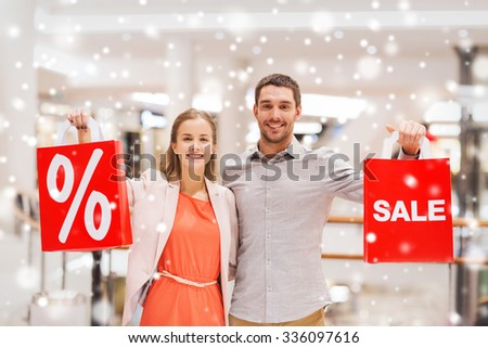 sale, holidays, discount, consumerism and people concept - happy young couple with red shopping bags in mall with snow effect - stock photo