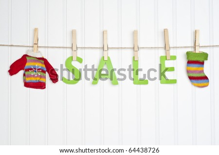 SALE on a Clothesline with Warm Winter Clothing.  Holiday Concept. - stock photo