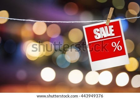Sale paper label in photo frame paper hanging on bright spot blurred background, discount banner. - stock photo