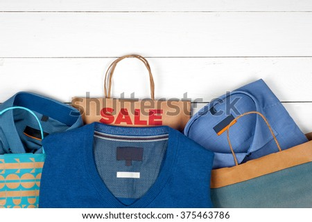 Sale. Paper shopping bags, men's shirts and tie on a white  wooden background. Space for text. Top view