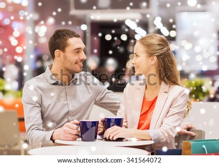 sale, shopping, consumerism, leisure and people concept - happy couple with shopping bags drinking coffee in mall with snow effect