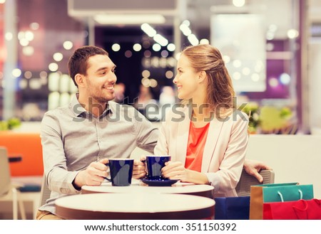 sale, shopping, consumerism, leisure and people concept - happy couple with shopping bags drinking coffee in mall - stock photo