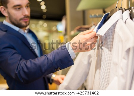 sale, shopping, fashion, style and people concept - close up of young man in suit choosing shirt in mall or clothing store - stock photo