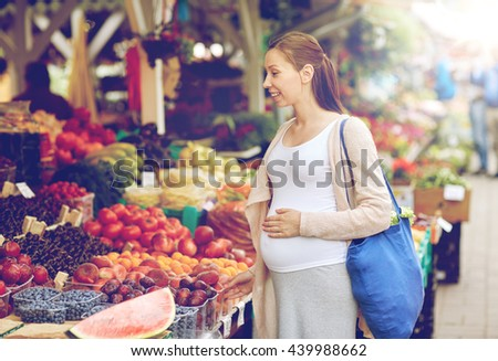 sale, shopping, pregnancy and people concept - happy pregnant woman choosing food at street market - stock photo
