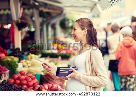sale, shopping, pregnancy and people concept - happy pregnant woman with wallet and credit card buying food at street market - stock photo