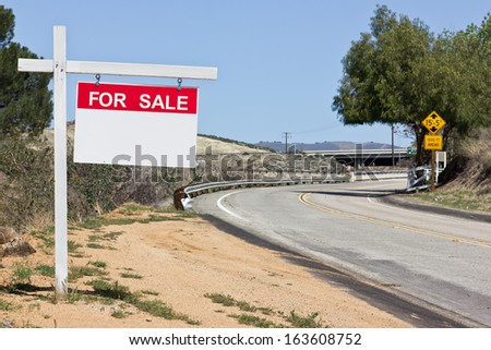 Sale sign hangs off a wooden post in a rural scene.  - stock photo