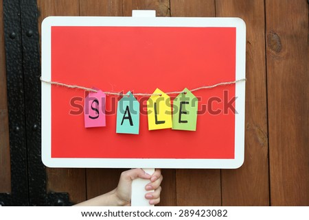 Sale sign on wooden fence background - stock photo