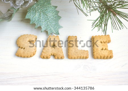 Sale sign written with cookies on the white painted wooden background with Christmas decor. Toned image.