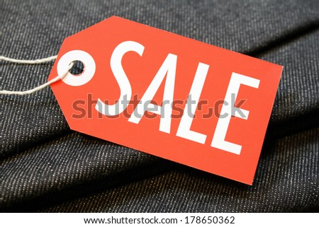 Sale tag with string on denim cotton material - stock photo