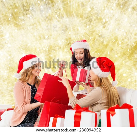 sale, winter holidays, christmas and people concept - smiling young woman in santa helper hat with gifts and shopping bags over yellow lights background - stock photo