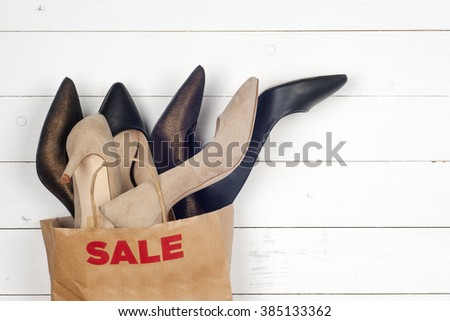 Sale women shoes in high heels and shopping bags: consumerism concept - stock photo