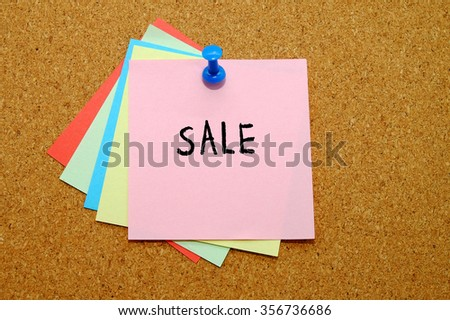 Sale written on color sticker notes over cork board background.