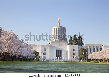 SALEM, OREGON - MARCH 23, 2014: Capitol State Building against a blue sky. Cherry Blossom Trees Blooming at Oregon State Capitol State Park in Salem Oregon during springtime. A tourist attraction. - stock photo