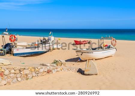 SALEMA BEACH, PORTUGAL - MAY 15, 2015: typical fishing boats on beach in Salema coastal village. Algarve region is popular holiday tourist destination on coast of Portugal. - stock photo