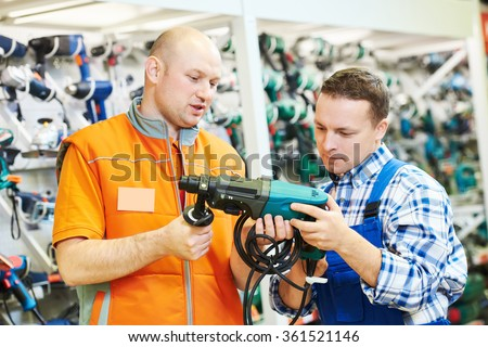 Sales assistant at work. male hardware store worker helps to choose drill or perforator to buyer customer  - stock photo