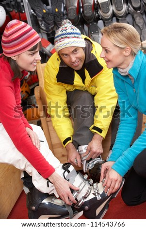 Sales Assistant Helping Couple To Try On Ski Boots In Hire Shop - stock photo