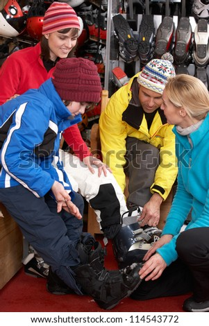 Sales Assistant Helping Family To Try On Ski Boots In Hire Shop - stock photo