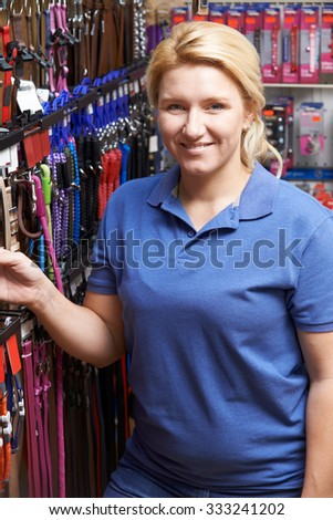 Sales Assistant In Pet Store With Display Of Dog Leashes - stock photo