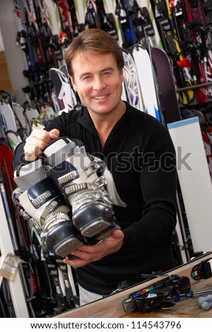 Sales Assistant With Ski Boots In Hire Shop - stock photo