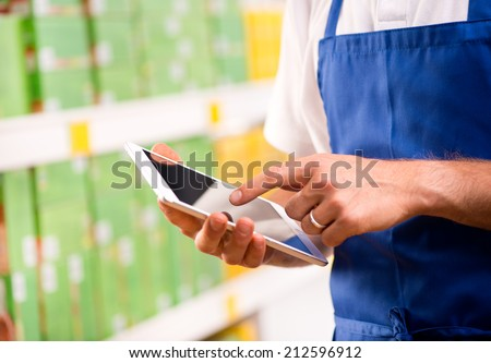 Sales clerk wearing apron using a digital tablet with store shelves on background. - stock photo